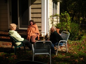 Three women gather in the back yard.